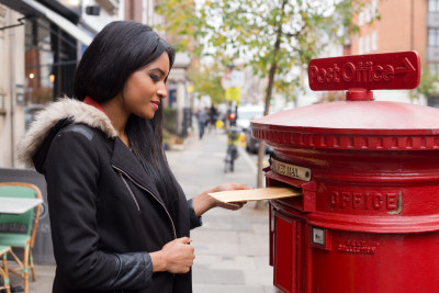 young woman posting a letter.