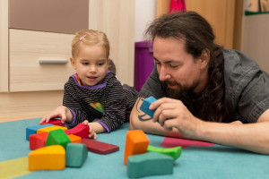 Man and toddler playing with bricks.